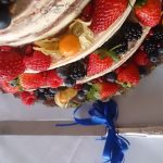 Bespoke Wedding Cakes Personalised wedding three tiers cake served on a wooden log, flavours were apple crumble, white chocolate and lemon, decorated with fresh berries