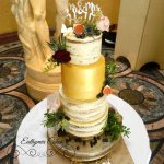 Semi naked gold wedding cake with gold tier and fresh flowers and berries