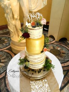 Semi naked wedding cake with gold tier and fresh flowers and berries