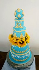 Blue and gold wedding cake with sunflowers