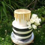 Butter cream cake with golden drip and black and white stripes, fresh flowers