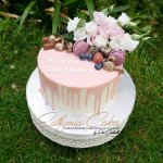 Gluten free carrot cake with chocolate drip, fresh flowers and macarons
