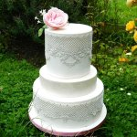 White and pink wedding cake with edible lace